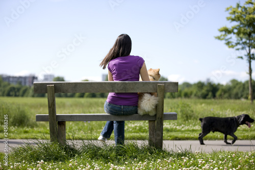 A young woman and her dog sitting on a bench