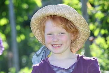 Fröhliches junges Mädchen mit Strohhut