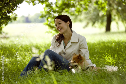 A young woman sitting on the grass with her dog