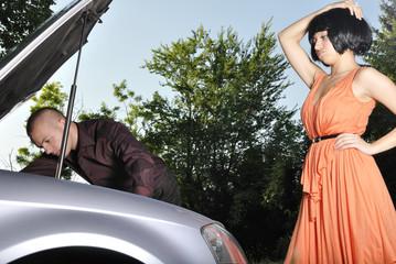 man fixing car for woman