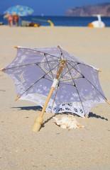 weißer Schirm am Meeresstrand