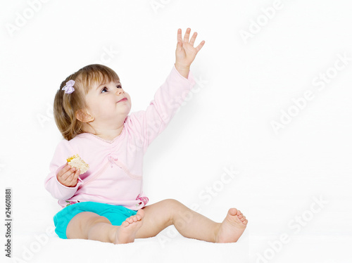 The little girl with the stretched hand on a light background