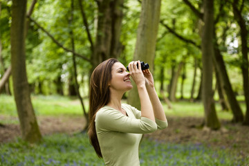 A young woman looking through binoculars, smiling