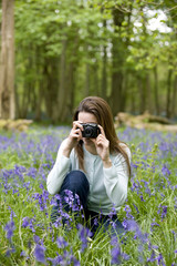 A young woman photographing bluebells