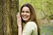 A young woman leaning against a tree, laughing