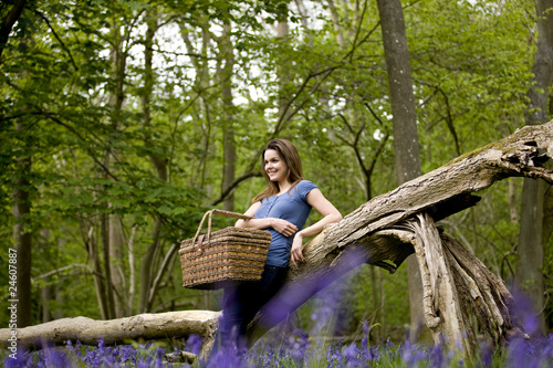 A young woman leaning against a tree, holding a picnic basket