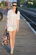 young woman wearing sunglasses, walking on platform