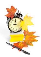 Alarm clock, autumn leaves, pen and stacked  blank papers