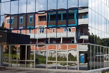 Rohbau eines Wohnhauses spiegelt sich in Fassade