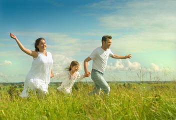 Happy family running on a meadow