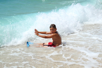 small boy sitting and stopping waves on sea