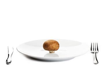 ein brauner champignon auf einem teller mit besteck