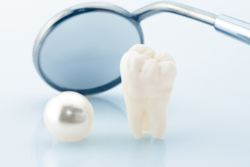 Real human wisdom tooth, natural pearl and dental mirror