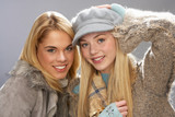 Two Fashionable Teenage Girls Wearing Cap And Knitwear In Studio poster