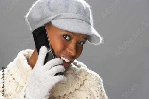 Fashionable Woman Wearing Knitwear And Cap In Studio Using Mobil