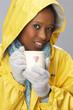 Young Woman Drinking Hot Drink Wearing Yellow Raincaot