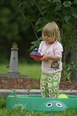 Little blond girl playing in sandbox