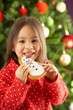 Young Girl Eating Cookie In Front Of Christmas Tree