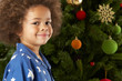 Young Boy Standing Next To Christmas Tree