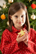 Young Girl Eating Star Shaped Christmas Cookie In Front Of Chris