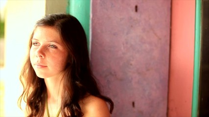 A serious teen leaning against a colorful wall.