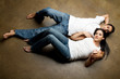 Sexy youngethnic casual couple relaxing on the floor
