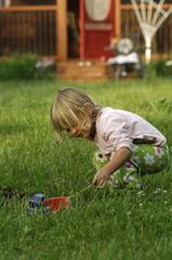 Little blond girl playing in garden