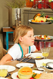 little girl sitting at breakfast table