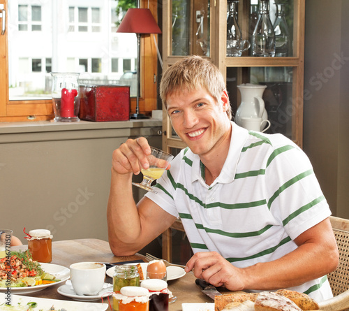 man sitting at breakfast table and smiling