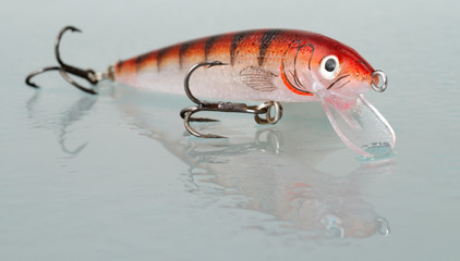 fishing lure on a wet glass with reflection