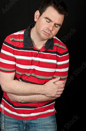 male having chest pain on black backdrop