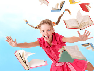 Schoolgirl  holding pile of books. Outdoor.