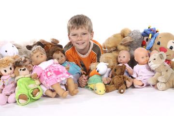 Bub mit Puppen und Kuscheltieren