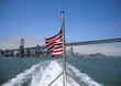 Tathered USA flag waves in the wind on the back of a ferry with
