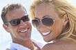 Leinwanddruck Bild - Happy Attractive Woman and Man Couple In Sunglasses At Beach