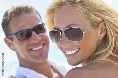 Leinwanddruck Bild Happy Attractive Woman and Man Couple In Sunglasses At Beach