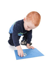 Boy finishing puzzle with last piece