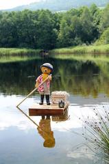 Teddy als Fährmann am Floß überquert See