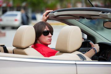 Young man driving a convertible.