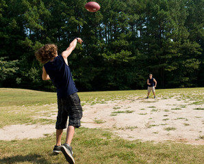 boy throwing football to his brother