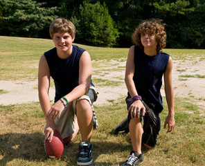 two teen boys posing with football, kneeling