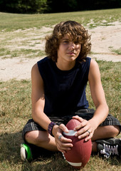 boy with long curly hair sitting, with football