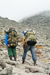 Two tired backpackers in mountains with knapsacks