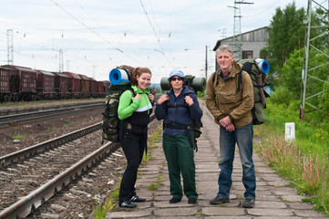 Group of travelers backpackers on railway station waiting train