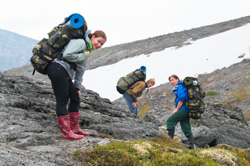 Tired team of backpackers in mountains with knapsacks