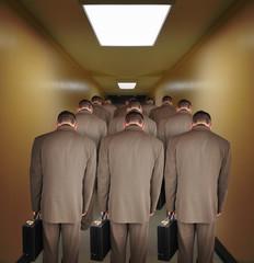 Overworked Business Men Walking down Hallway