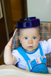 Baby with plate on head.