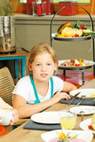 little girl sitting at breakfast table and looking at camera