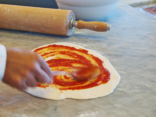 pizza baker preparing dough and topping