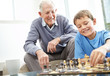 Grandfather and his grandson playing chess together